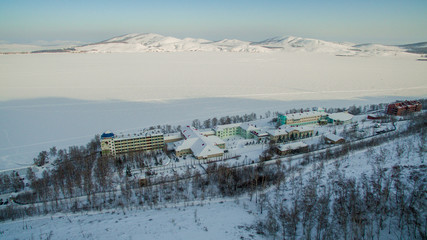 Resort on frozen lake in the mountains. Aerial. Ural, Russia