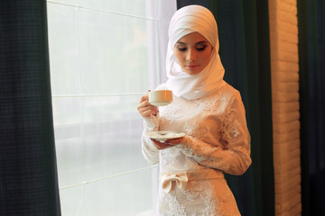 beautiful Muslim woman in a white wedding dress with a cup of tea in his hands