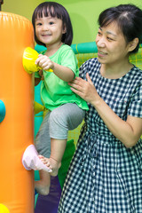 Asian Chinese mother and daughter playing at indoor playground