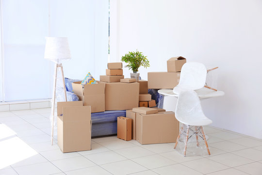 House moving concept. Boxes and furniture in new room