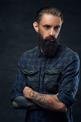 Bearded hipster male with crossed arms.