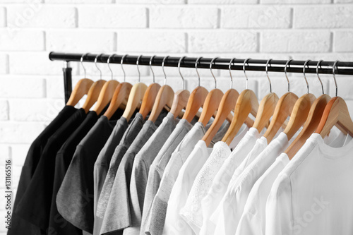 Black, grey and white t-shirts on hangers against brick wall