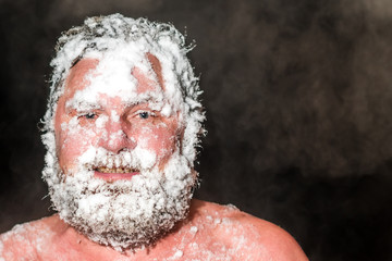 Adult bearded man covered with snow in the sauna