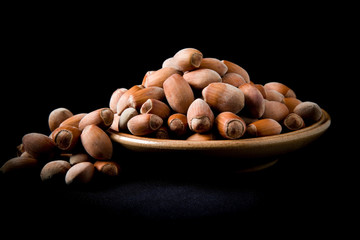 Nuts in the dish on black background for special atmosphere. Healthy eating and lifestyle.