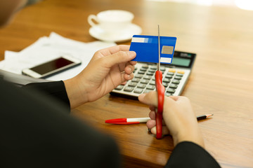 Concept bad finance woman is cutting credit card with scissors