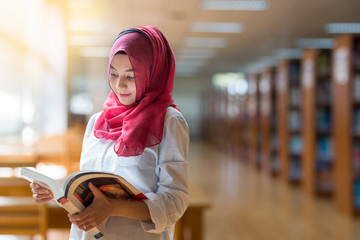 Beautiful Muslim girl reading book with hijab on blur library background.