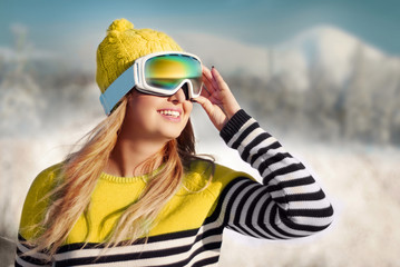 happy girl in a mask for snowboarding against the backdrop of sn