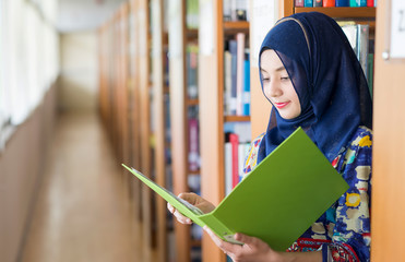 Muslim woman standing, holding document paper in library.