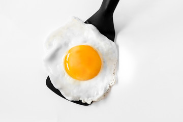 Tuinposter Gebakken Eieren Fried egg on a spatula