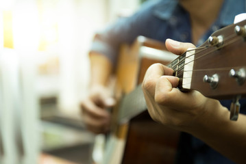 Selected focus man playing acoustic guitar  indoors