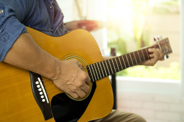 Selected focus man playing accousti guitar  indoors