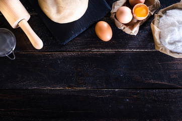 Ingredients for baking - dough, flour, wooden spoon, rolling pin, eggs, egg yolks on white background. Free space for your text