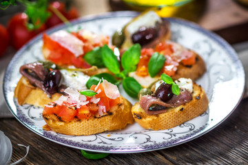 Tasty homemade bruschetta on wooden background