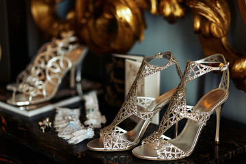 Silver wedding shoes stand on the black marble table