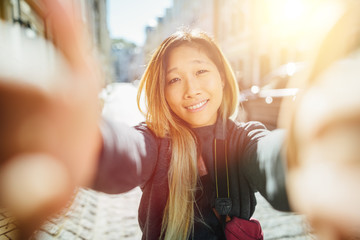 Travel Vacation Tourist Selfie. Asian Woman taking self-portrait photo on Europe. Girl on summer vacation visiting famous tourist destination having fun smiling