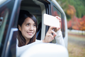 Woman taking photo outside a car