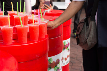 Refreshing red colorful, fruity drinks woman hand pick up taking