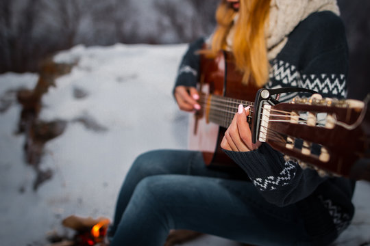 Girl playing guitar in the mountains near the fire burning