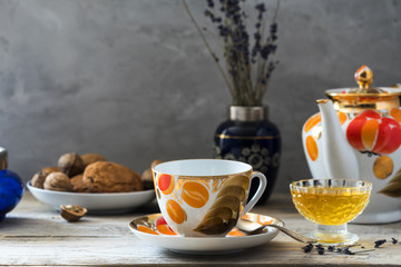 vintage old fashioned cup set with painted in orange and gold colors full with hot tea on table of light woods with crystal plate of sweet yellow honey, plate of oaten cookies and vase with lavender
