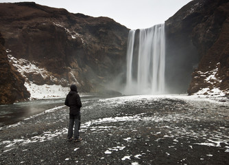 Man looking at Skogafoss waterfall, Iceland