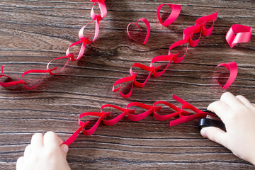 The child makes crafts out of paper garland for Valentine's Day.