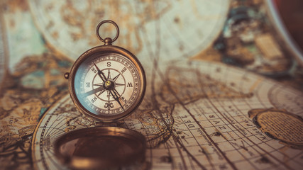 Antique compass and old world map.