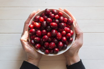 Cranberries in a bowl, held in a womans hands.
