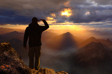 Man standing on a mountain watching sunset sunrise