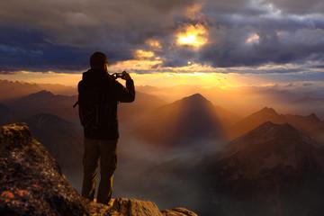 Wanderer auf Berggipfel macht Foto mit Smartphone