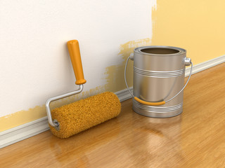Paint roller and can of paint near wall