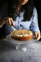 Female cutting a cake topped with cream cheese frosting and walnuts