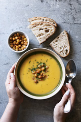 Female hands holding a bowl with pumpkin and roasted chickpea  soup.Top view