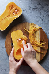 Female hands making butternut squash noodles with a vegetable peeler.Top view.