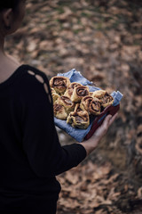 Woman holding tray full of cinnamon rolls outdoors