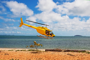 helicopter flies over the beach
