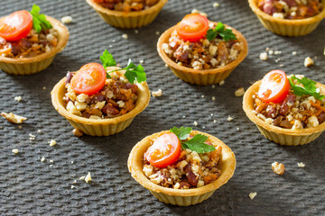 Holiday appetizer: tartlet with beans, meat and walnuts on a fes