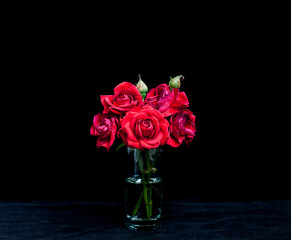 Bouquet of red roses  in crystal glass on velvet textured table cloth. Floral wallpaper