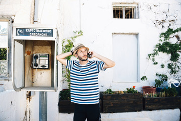 Greece, Milos, Klima, Man talking on cell phone, leaning against old telephone booth
