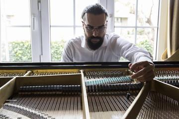 Piano tuner tuning grand piano