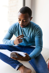 Young man reading a booklet sitting by the window
