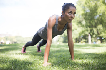 Woman doing push-ups on meadow in park