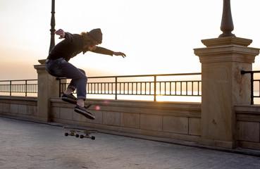 skater boy skating on seaside during sunset