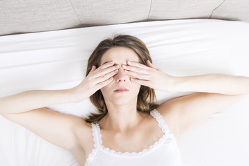 Young sleeping woman in bedroom at home wearing in white