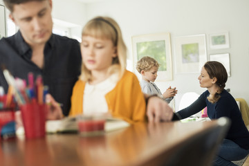 Father assisting daughter with mother talking to boy at home