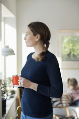 Woman standing with coffee cup in living room at home