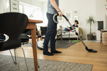 Low section of father cleaning floor with vacuum cleaner at home