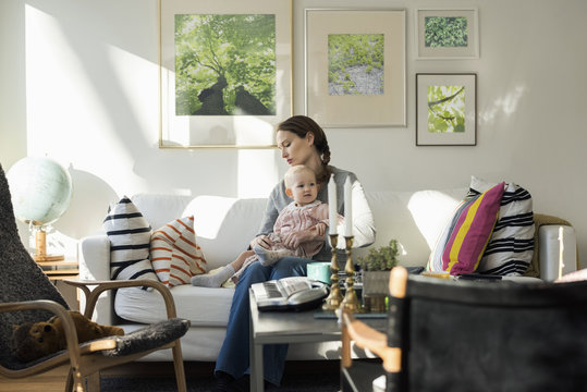 Woman sitting with baby girl on sofa at home