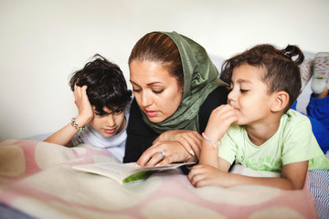 Mother reading book to boys while lying on bed at home