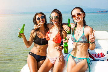 Three beautiful cheerful wet hipster girl at the beach on a tropical island, sitting on the speedboat, drink beer, merry company, sexy bikinis, sunglasses, crazy emotions, grimace, speed boat, sea
