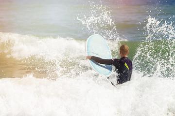 beginner surfer fighting with big waves